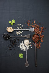 Raw rice of different types, black wooden surface, above view