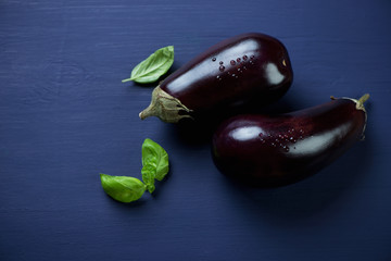 Fresh aubergines over dark blue wooden surface, high angle view