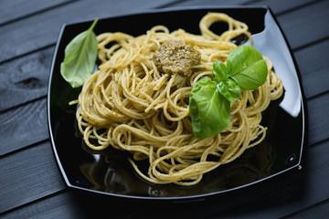Spaghetti with pesto sauce and fresh green basil leaves