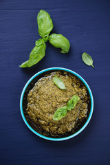 Close-up of freshly made pesto, dark blue background, above view
