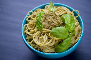 Close-up of spaghetti with basil pesto in a glass bowl