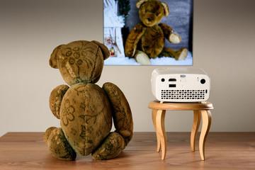 Teddy Bär, der mit einem Mini Projektor seine Fotos anschaut. D