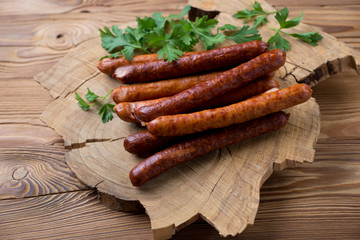 Smoked sausages with parsley over rustic wooden background