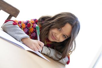 Niña con poncho de colores escribiendo