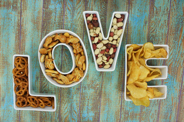 Snacks in Love shaped letter bowls on rustic background