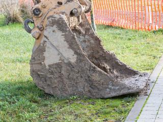 closeup of muddy excavator shovel on grass near construction are