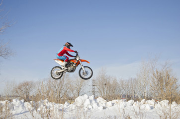 MX driver on the motorcycle is flying over the hill snow