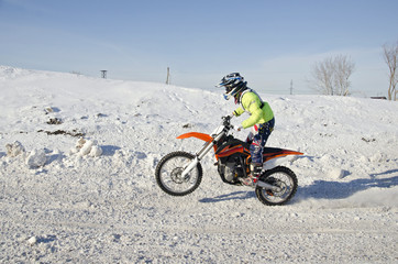 Winter Motocross racer rides standing up on the rear wheel