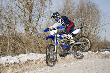 Motocross, motorcycle driver flies over hill out of snow
