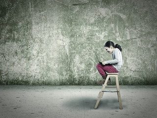 kleines Kind auf der Leiter mit einem Laptop