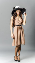 Cheerful brunette girl in summer dress and hat