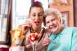 canvas print picture - Oma und Enkelin essen Eisbecher im Cafe