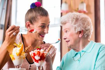 Oma und Enkelin essen Eisbecher im Cafe