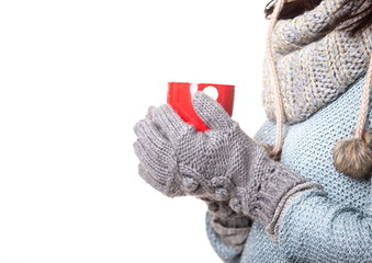 Hands in knitted mittens holding a red circle, isolated on white