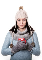 Girl in a knitted hat with a red circle with a coffee in hand is
