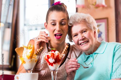 canvas print picture Oma und Enkelin essen Eisbecher im Cafe
