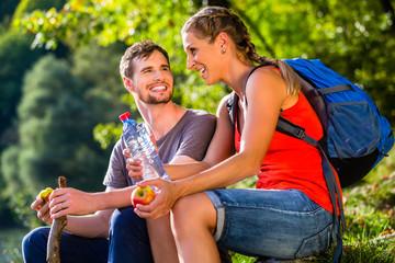 Paar bei Wandern im Sommer trinkt Wasser