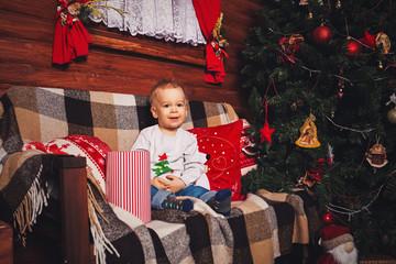 Cute little boy sits near a festive Christmas tree