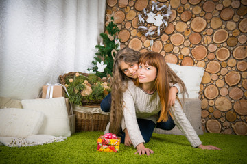 Mother and daughter hugging, winter evening together at home,
