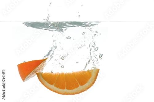 canvas print picture frische Orangespalten tauchen ins Wasser