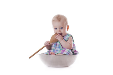 baby girl holding wooden spoons