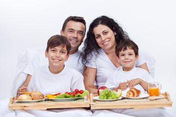 Happy family having breakfast in bed