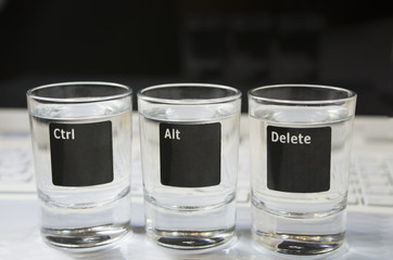 """Laptop keyboard with """"Ctr-Alt-Delete""""  pictured on 3 glasses"""