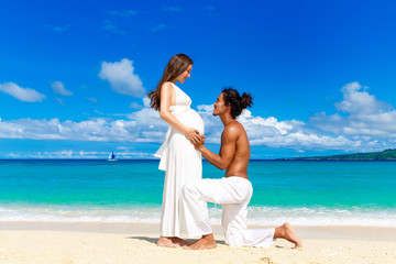 Happy and young pregnant couple having fun on a tropical beach.
