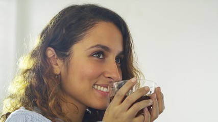 Attractive young woman smiling whilst holding her hot drink