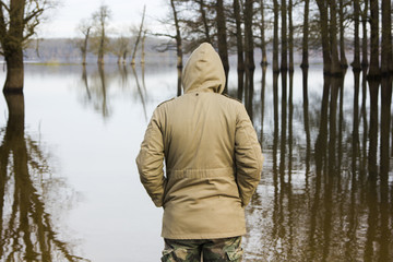 Man in jacket and military pants observing the river