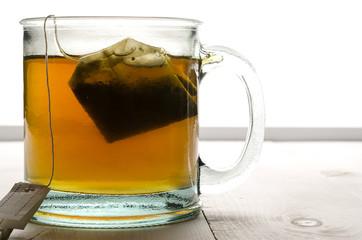 Glass of tea and tea bag back lit