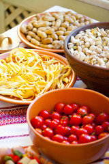 close up of a bowl of pistachio nuts, cheese, peanuts, cherry to