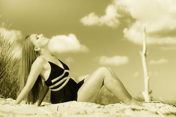 Woman sunbathing on beach.