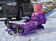 Little girl sliding with sledding on route. Danger