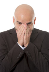 businessman covering face with hands in stress