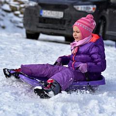 Little girl sliding with sledding on route. Danger