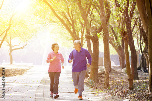 happy Senior Couple Exercising In the Park - 76452388