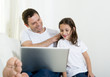 father on couch with young daughter using computer laptop