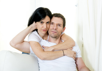 attractive couple woman hugging husband in couch smiling happy