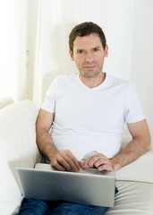 attractive man at home lying on couch working with computer