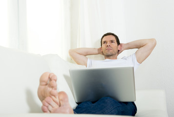 attractive man at home couch daydreaming with computer work