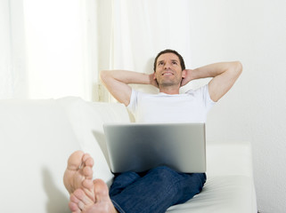 attractive man at home daydreaming with computer work