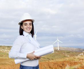 Female engineer holding blueprints at wind turbine site