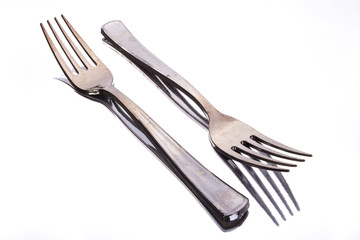 Couple of forks reflection on white background