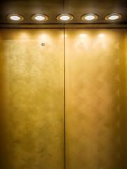Gold metal door of elevator with spotlights