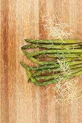 Fresh grilled asparagus and parmesan cheese on a timber board.