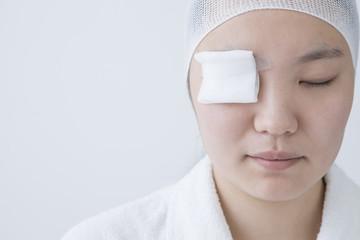 Woman wearing a gauze in one eye
