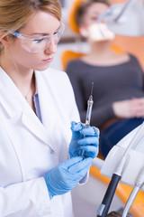 Stomatologist holding syringe