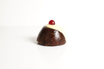 Pudding with custard and cherries on a white background.