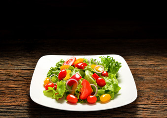 Fruit and vegetable salad on a plate on wooden table